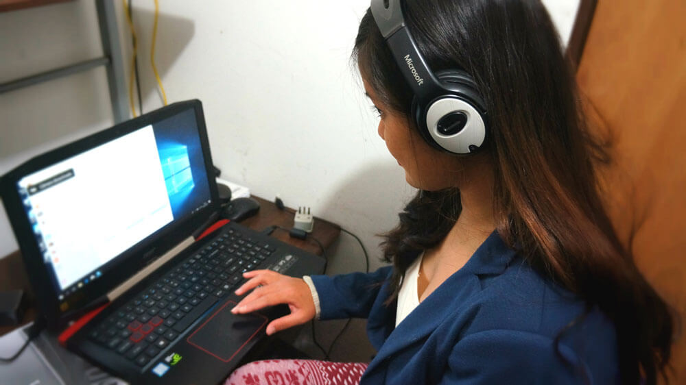 BridgeTEFL grad and author of this blog post, Krzl wearing a headset while she prepares to teach English online from home.