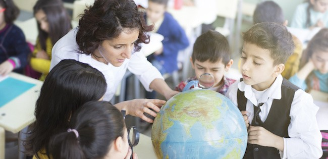 Teacher with students looking at globe