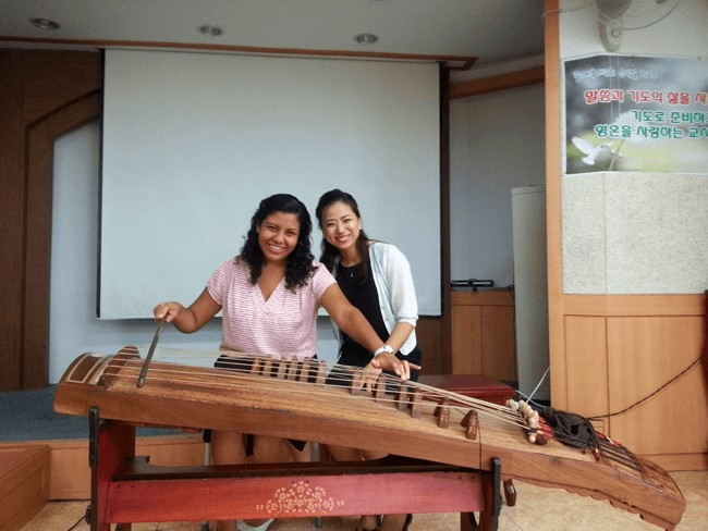 "Gedisa, English teacher in Korea, receives a lesson on the ""gayageum,"" a traditional Korean instrument"