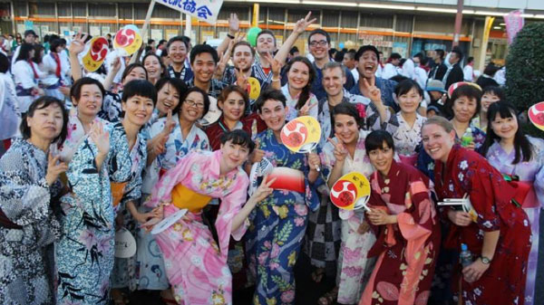A Bridge student posing with her English learners while teaching abroad in Japan.