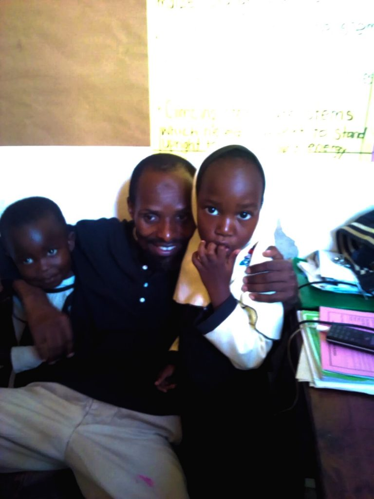 teacher Badiru with two young students