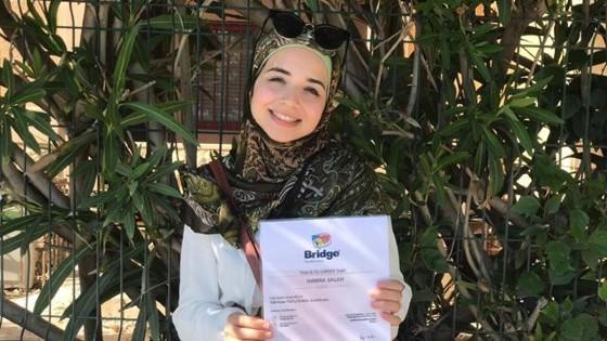 Hawra holding her Bridge TEFL/TESOL certificate