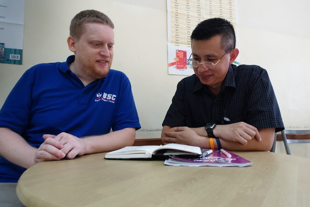 Brandon, from the U.S., tutoring one of his adult students in Thailand.