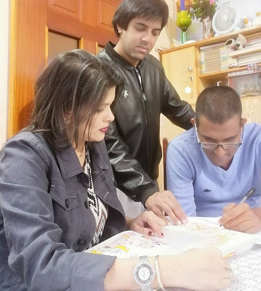 Shakti helping his little brother and older sister with their English and French homework
