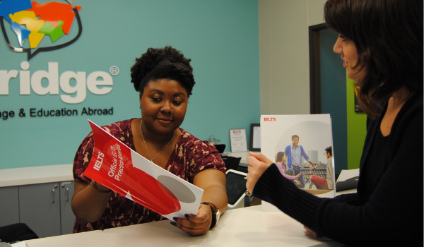 A student speaking with the receptionist about the IELTS test prep course at Bridge in Denver, CO.