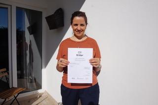 Margarida holding her Bridge TEFL/TESOL certificate